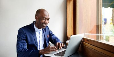 51498327 - portrait of happy african businessman sitting in a cafe and working on laptop